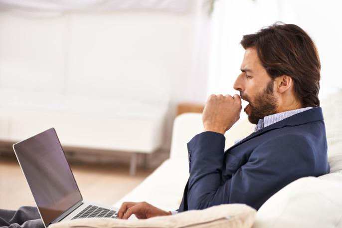 http://A%20handsome%20businessman%20yawning%20while%20working%20on%20his%20laptop